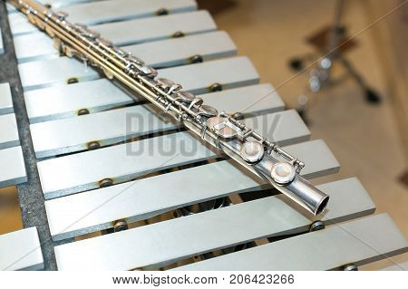 symphonic and brass band, percussion and wind instruments concept - beautiful closeup on western concert flute lies on xylophone beige bars, military, marching, orchestra, ensembles, jazz concert