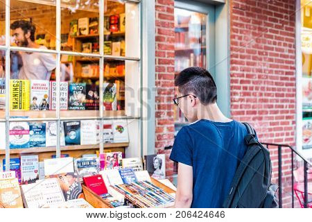 Washington Dc, Usa - August 4, 2017: Closeup Back Of Young Asian Man Student Boy Checking Out Used B