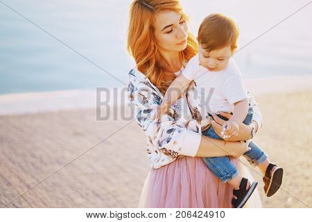 Beautiful red-haired woman with her wonderful son on a summer city