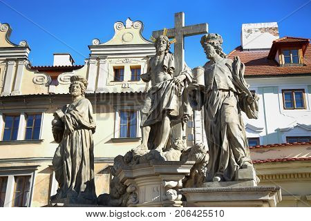 Statuary of Christ the Saviour with St. Cosmas and St. Damian on the Charles Bridge (Karluv Most) in Prague Czech Republic