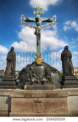 Statuary of the St. Cross with Calvary on the Charles Bridge (Karluv Most) in Prague Czech Republic