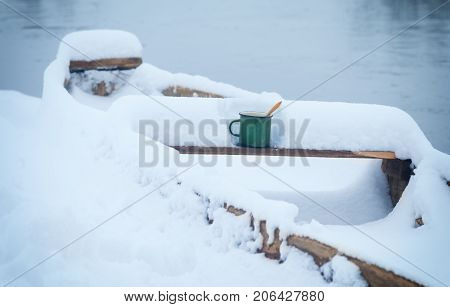 hot tea in cold winter.wooden boat on the Bank of winter river
