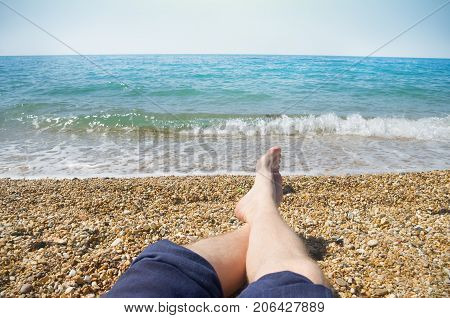 male bare feet on background of sea beach
