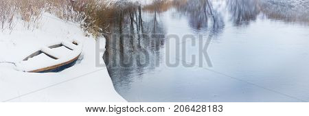 wooden boat on snowy river banks in winter