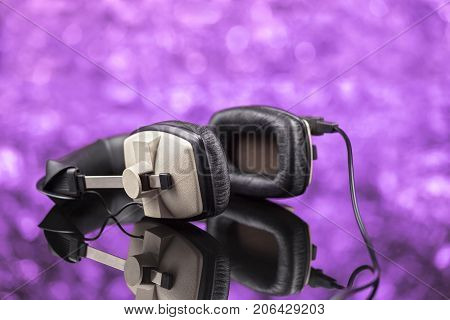Professional Stereo Headphones On Violet Background Out Of Focus