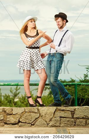 Summer holidays love relationship and dating concept - romantic playful couple retro style flirting outdoor