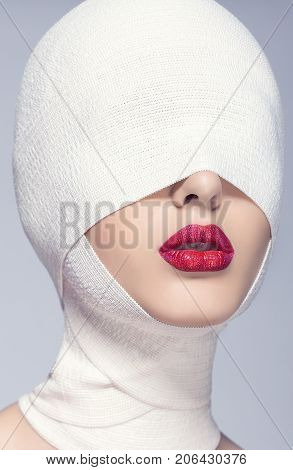 Beautiful woman with bandages on her head, her face beautiful red lips. Lovely portrait of a female face in bandage with red lipstick.