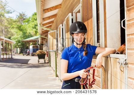 Portrait of happy young woman in jockey wear standing by riding stables and holding reins in her hands