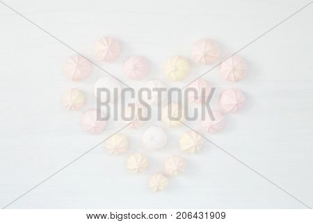 Meringues white wooden bacground pastel colors texture pink heart