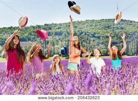 Joyful age-diverse kids standing in lavender field and tossing up hats at summer's day