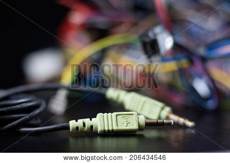 Old Entangled Cables, Electronics And Old Cable Connectors On A Black Table.