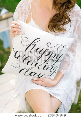 congratulation, interior, design concept. charming young bride dressed in short white dress with laces holding sweet element of decoration, little cushion with italic words happy wedding day