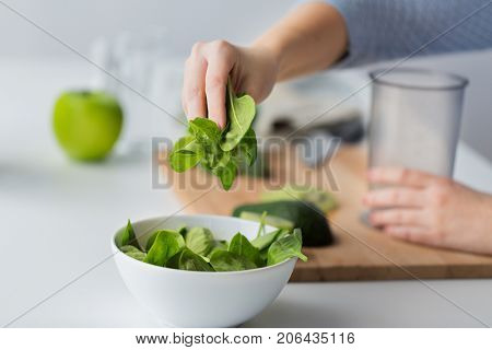 healthy eating, baby food, diet and cooking concept - close up of woman hand adding spinach leaves to bowl