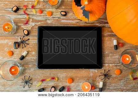 holidays and technology concept - pumpkins, candies, candles and tablet pc computer on wooden table