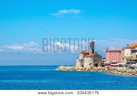 Beautiful view of the rocky promontory with a small lighthouse and a tower dedicated to the church of Sts. Clement, Piran, Slovenia, Europe