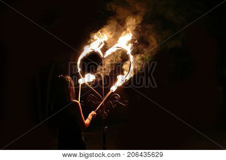 fire performance, wedding, sentiment concept. in the dark of night female performer taking two torches and lightening huge heart, world known symbol of love and marriage