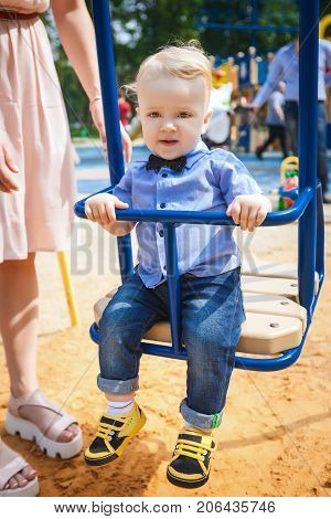 nice boy swinging on blue swing in amusement park, joyful child walking with his mother in park, concept of happy family