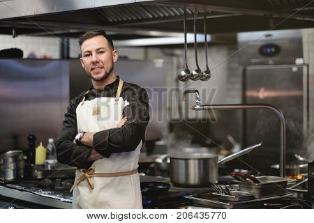 Food concept. A young cook stands in the kitchen. He crossed his arms over his chest and looked confidently forward.