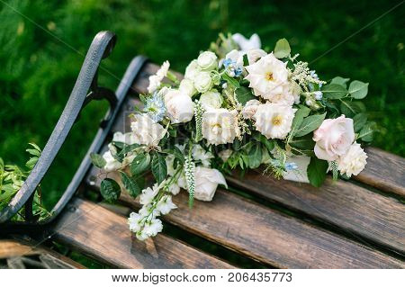 floral design, sentiment, present concept. on the bench of park there is forgotten bouquet of marvelous flowers, elegant roses and avalanches in white and light pink shades
