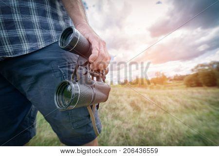 Man backpacker on the trail holding binoculars