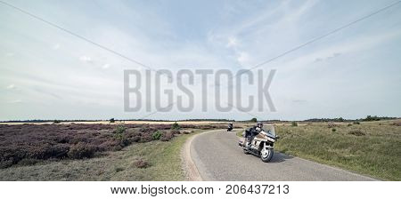 National Park Hoge Veluwe - Septembe 17 2017: Motor cyclist driving on country road in moorland.