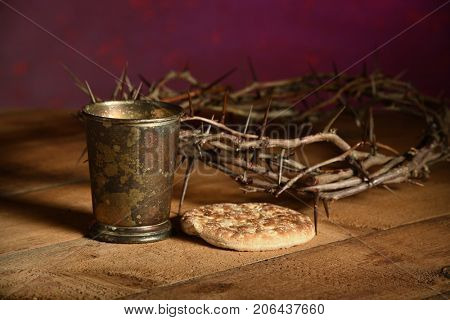 Communion elements with crown of thorns over vintage table