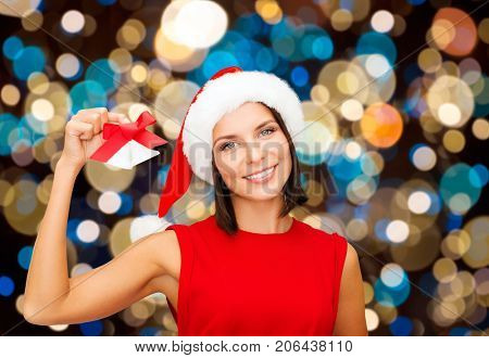 christmas, holidays and people concept - happy woman in santa hat with jingle bells over lights background