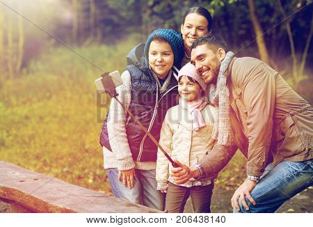 tourism, hike, technology and people concept - happy family taking picture with smartphone on selfie stick at camp