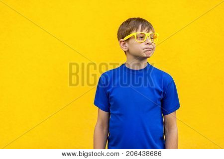 Dissatisfied And Unhappy Boy In Yellow Glasses, Loking Away.