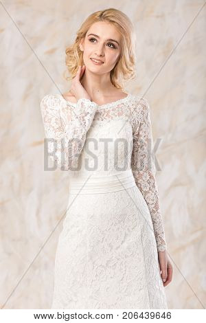 fashionable gown, beautiful blonde model, bride hairstyle and makeup concept - young smiling lady in white wedding exquisite dress stand indoors on a light background, slender pretty girl posing