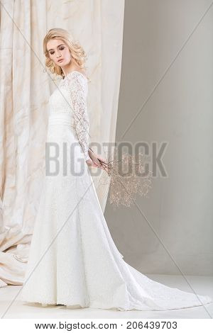 fashionable dress, beautiful blonde model, bride hairstyle and makeup concept - luxury young woman in white wedding gown standing indoors on light background, slim female posing with bouquet in hands