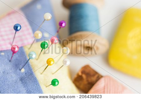 needlework, quilting, sewing and tailoring concept - colorful cute stitched pincushion with lot of beautiful pins, tools closeup on white desk, blue and pink thread spools, selective focus, top view