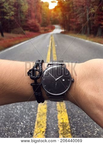 Man checking time on the stylish watch at scenic forest road. Men's accessories watch and wristband concept.
