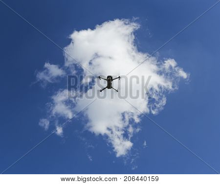 Professional camera drone flying under the clouds