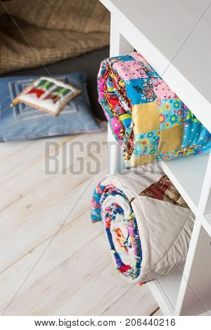patchwork, sewing and fashion concept - two colorful quilted bedspreads in studio at white shelves with few storage compartments, warehouse of finished products, pillow on floor, top view, vertical