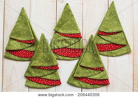 patchwork and quilting concept - closeup on decorative red-and-green napkins on a whitewashed wooden floor, festive embroidered towels in shape of Christmas trees, top view, flat lay