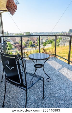 Light hotel balcony with view on pine forest and field. Chair, tables.