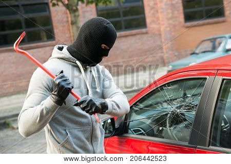 Close-up Of A Thief Wearing Balaclava Breaking Car Window With Crowbar