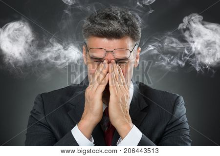 Portrait Of Businessman Covering Mouth From Smoke Over Black Background