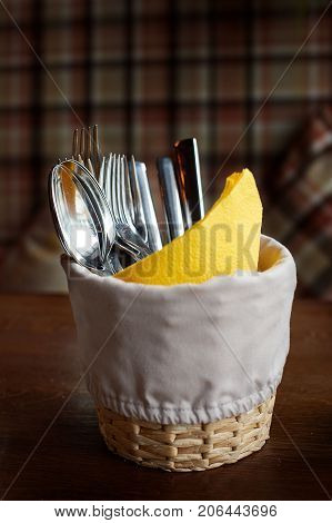 Steel flatware in a box with yellow napkin