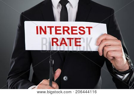 Close-up Of Businessman Cutting Paper With Interest Rate Text