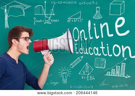 Male Teacher Announcing Online Education Through Megaphone In Classroom