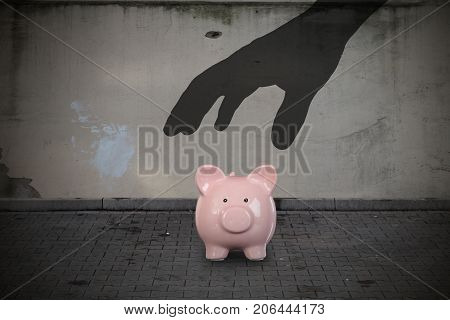 Close-up Of Silhouette Hand Picking Up Piggy Bank On Street
