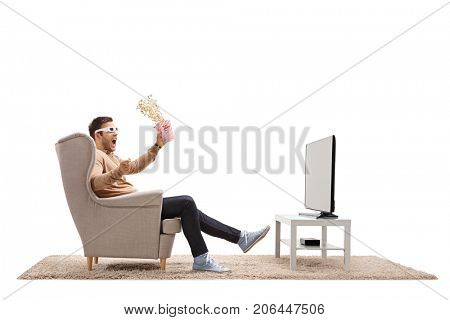 Terrified young man with 3D glasses and popcorn seated in an armchair watching TV isolated on white background