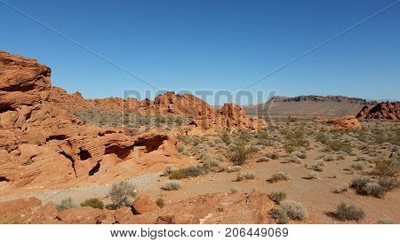 This scene is from the Nevada desert. Bushes, rocks and brush dot the floor of the desert giving it a lively texture.