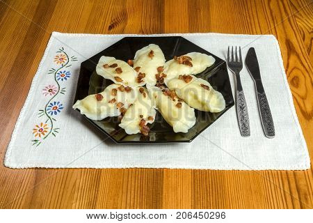 Cooked dumplings with cheese pork scratching on wooden table. Polish ukrainian russian traditional food.Fried dumplings with cheese and pork scratching on wooden table. Polish ukrainian russian traditional food.