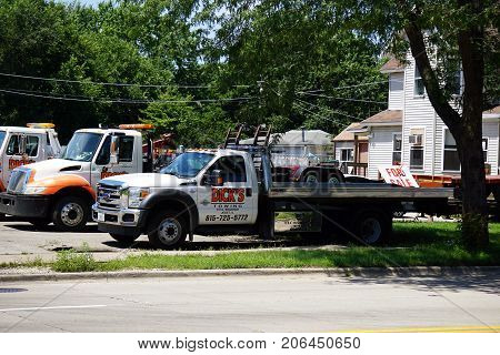 JOLIET, ILLINOIS / UNITED STATES - JULY 25, 2017: Tow trucks, belonging to Dick's Towing, are parked on the company's lot.