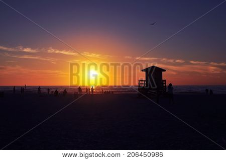 View of sunset in a beach with people and lifeguard base silhouette in frame.