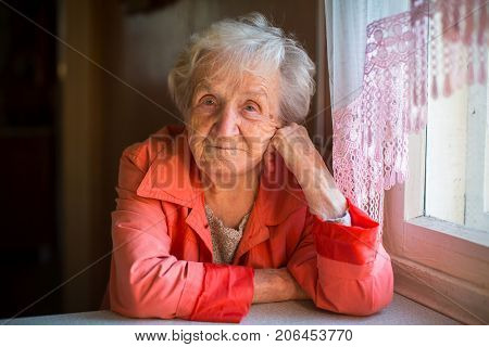 Portrait of elderly woman in the red sitting at table.