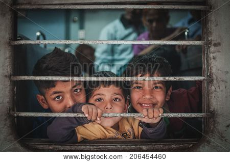Ajmer India : 18th February 2015 - Shot of three indian children looking happy with much anticipation and excitement travelling in a train.